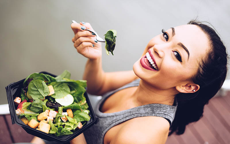 woman eating a salad full of leafy greens