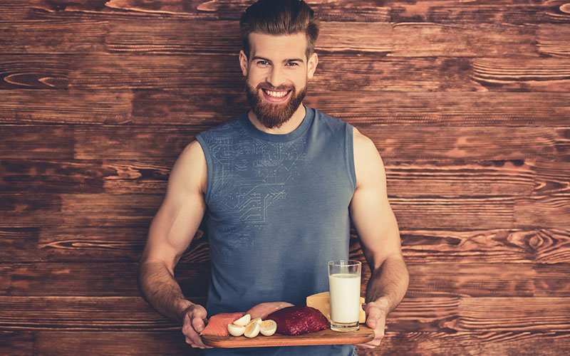 smiling man with muscle gaining foods on a tray